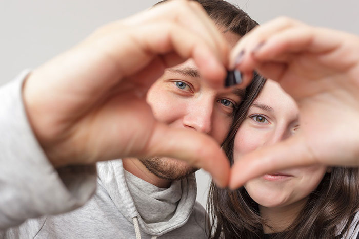 Two people making a heart with their hands